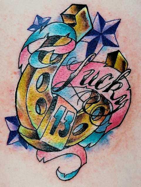 Tatuagem nas costas da menina - ferradura, as estrelas, o número 13 e a inscrição