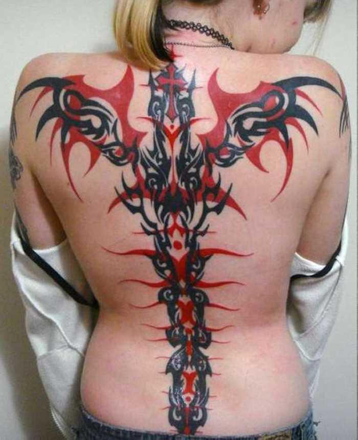 Tatuagem nas costas de uma menina - a cruz com o seu padrão