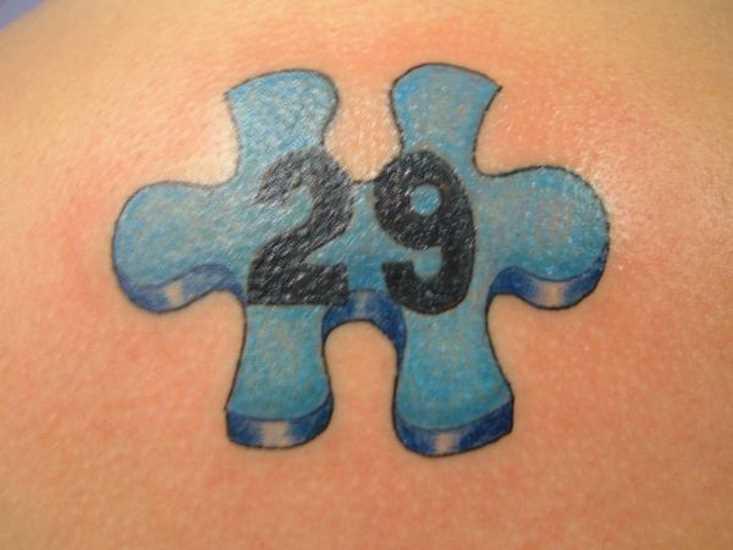 Tatuagem nas costas de uma menina de quebra - cabeça e o número 29