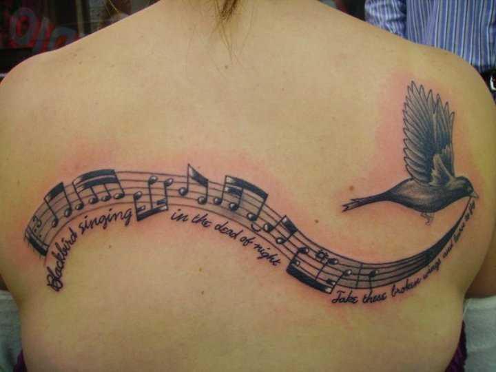 Tatuagem nas costas de uma menina nota, o pássaro e a legenda em inglês