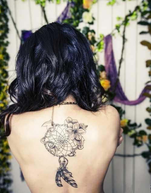 Tatuagem nas costas de uma menina - o apanhador de sonhos e flores