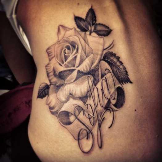 Tatuagem nas costas de uma menina - rosa e inscrição