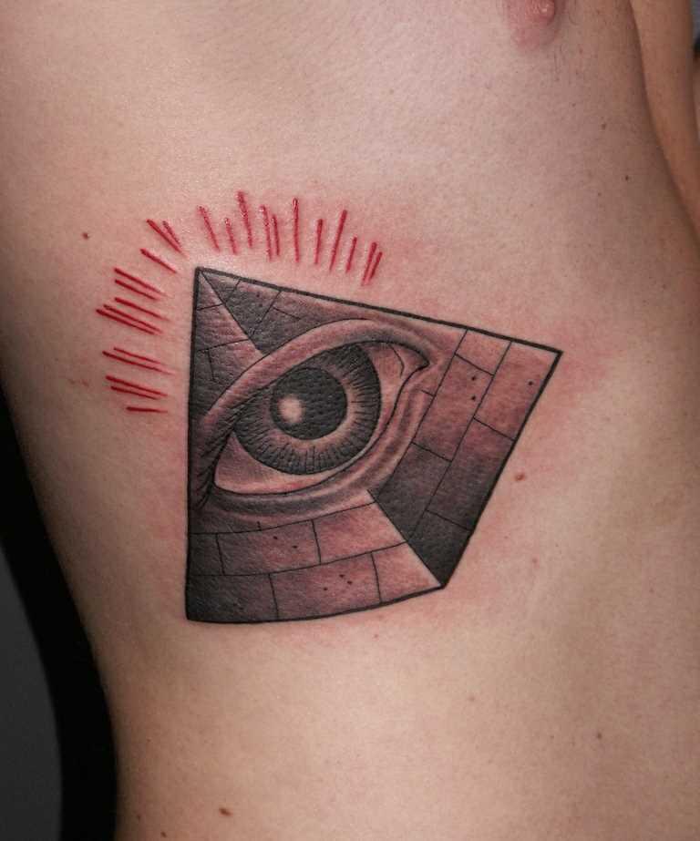 Tatuagem nas costelas de um cara em forma de pirâmide com o olho