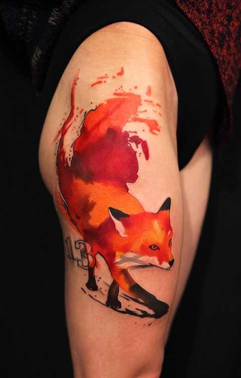 Tatuagem nas coxas da menina - a raposa e o número 13