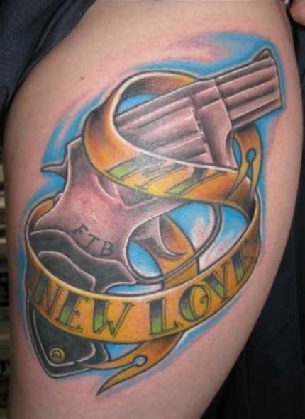 Tatuagem nas coxas da menina - arma e inscrição