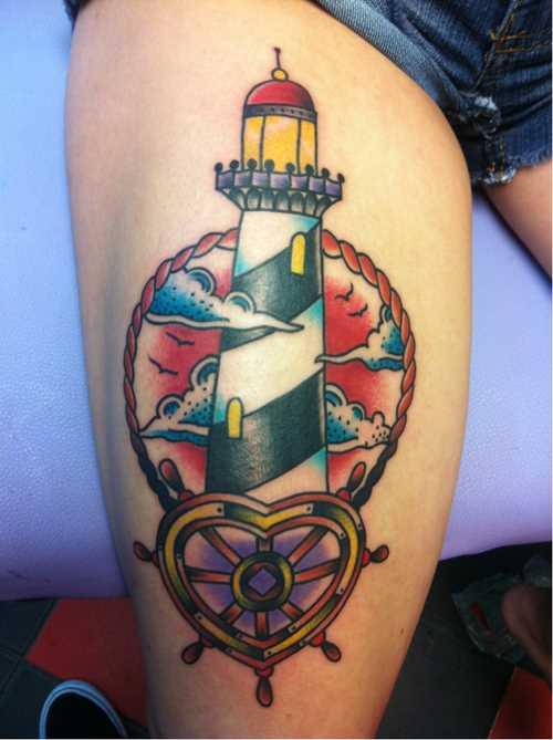 Tatuagem nas coxas da menina - farol e leme