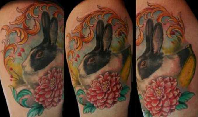 Tatuagem nas coxas da menina - lebre com uma flor e um padrão