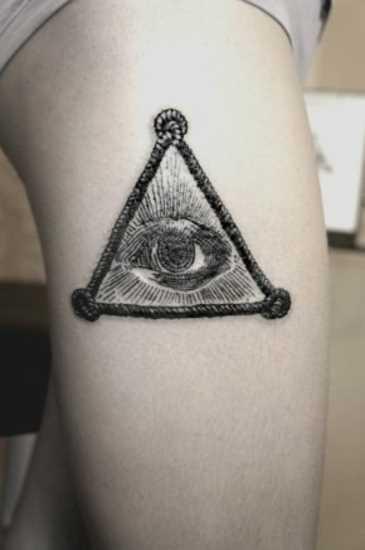 Tatuagem nas coxas da menina - triângulo com um olho dentro dele