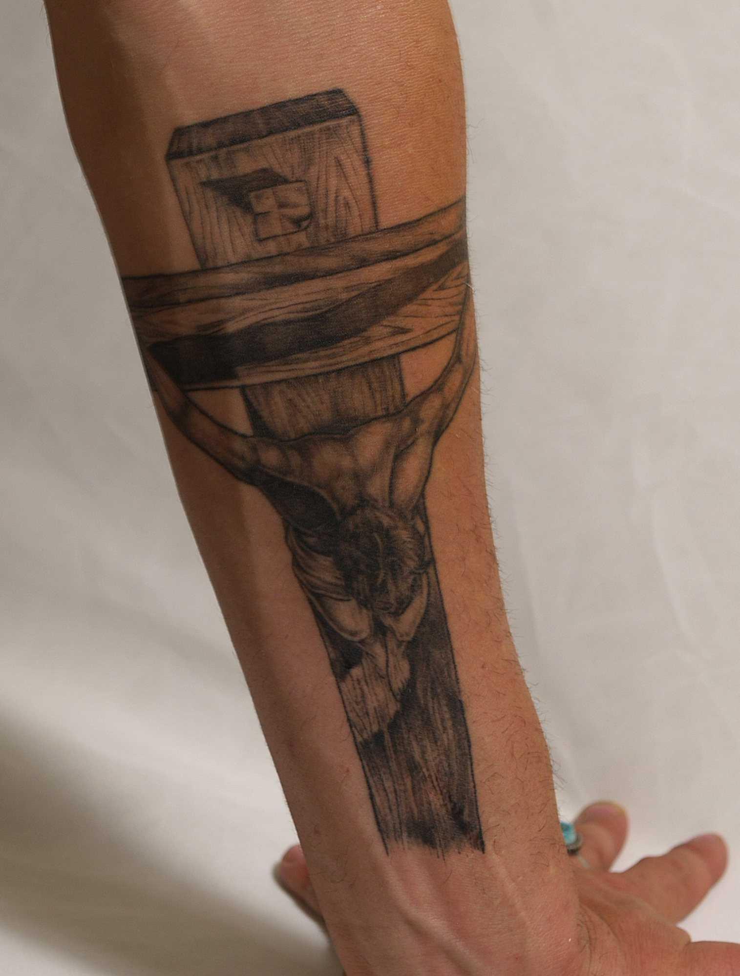 Tatuagem no antebraço cara - a cruz com o crucificado nela Jesus