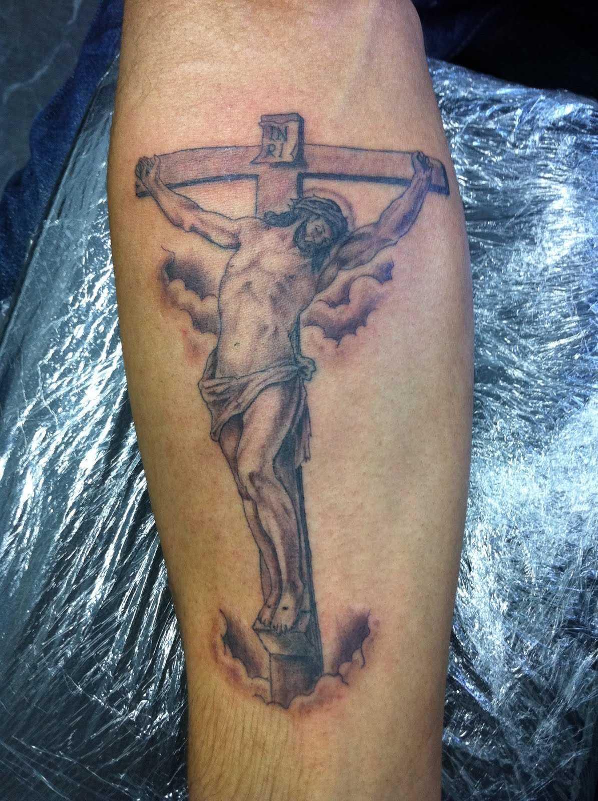 Tatuagem no antebraço cara - a cruz e o crucificado nele Cristo