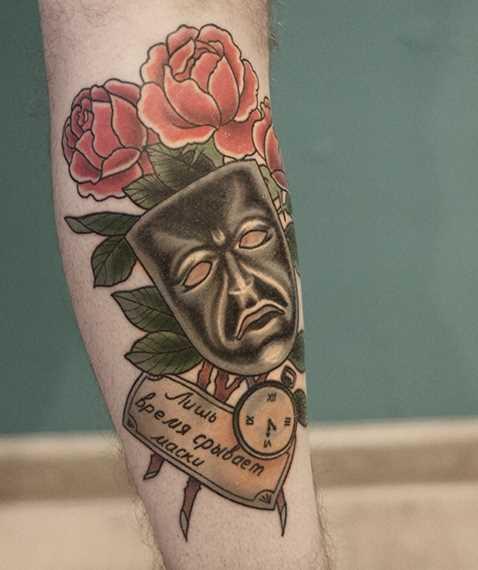 Tatuagem no antebraço cara - a máscara, rosas e inscrição