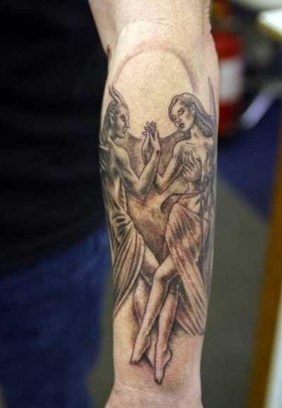 Tatuagem no antebraço cara - de- anjo e um demônio