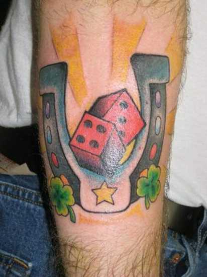 Tatuagem no antebraço cara - de- ferradura e o dado