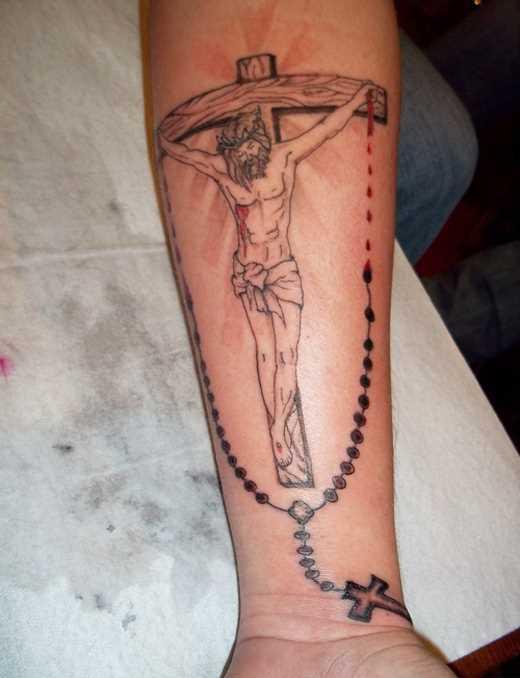 Tatuagem no antebraço da menina - a cruz com o crucificado Jesus e a cruz na cadeia