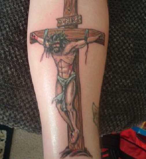 Tatuagem no antebraço da menina - a cruz e o crucificado nela Jesus