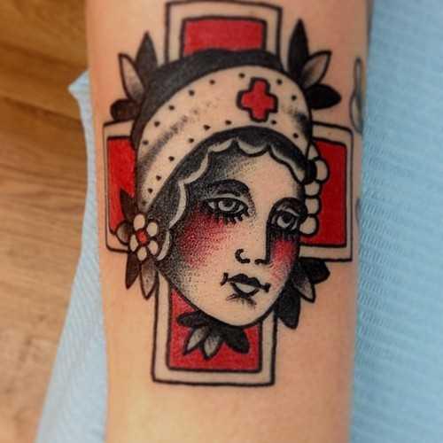 Tatuagem no antebraço da menina - a cruz vermelha e o rosto da menina-medsesry