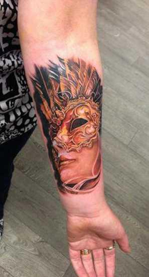 Tatuagem no antebraço da menina - a menina para dentro da máscara, com as suas penas