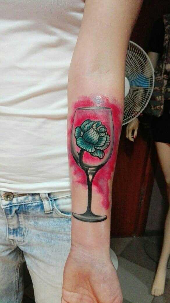 Tatuagem no antebraço da menina - rosa em uma taça
