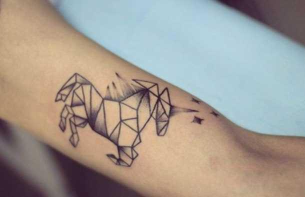 Tatuagem no antebraço da menina - um unicórnio e um asterisco