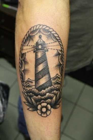 Tatuagem no antebraço de um cara em forma de farol