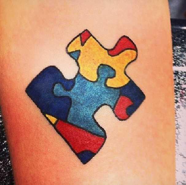 Tatuagem no antebraço de uma menina de quebra - cabeça dos pequenos quebra-cabeças