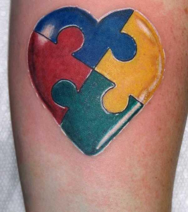 Tatuagem no antebraço de uma menina de quebra - cabeça em forma de coração