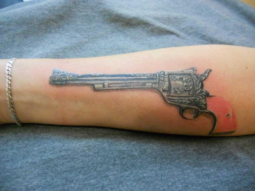 Tatuagem no antebraço do cara - a arma