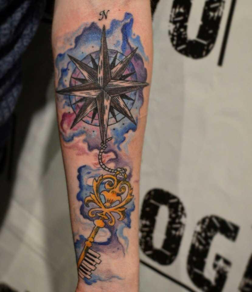 Tatuagem no antebraço do cara - chave e a rosa-dos-ventos