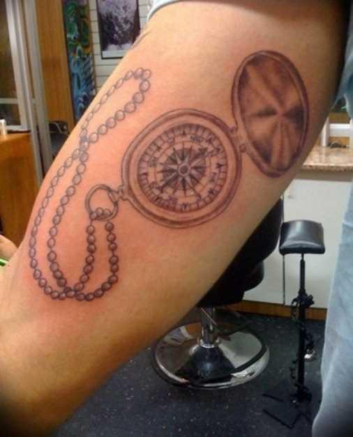 Tatuagem no antebraço do cara como uma cadeia com bússola