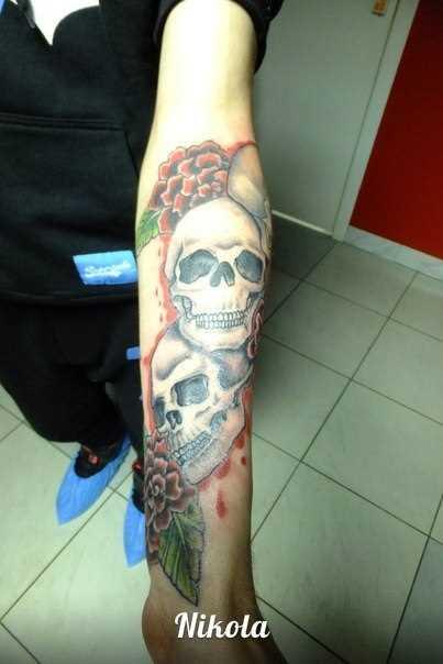 Tatuagem no antebraço do cara - de caveiras e flores