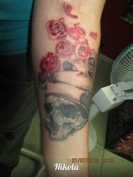 Tatuagem no antebraço do cara - de caveiras e rosas