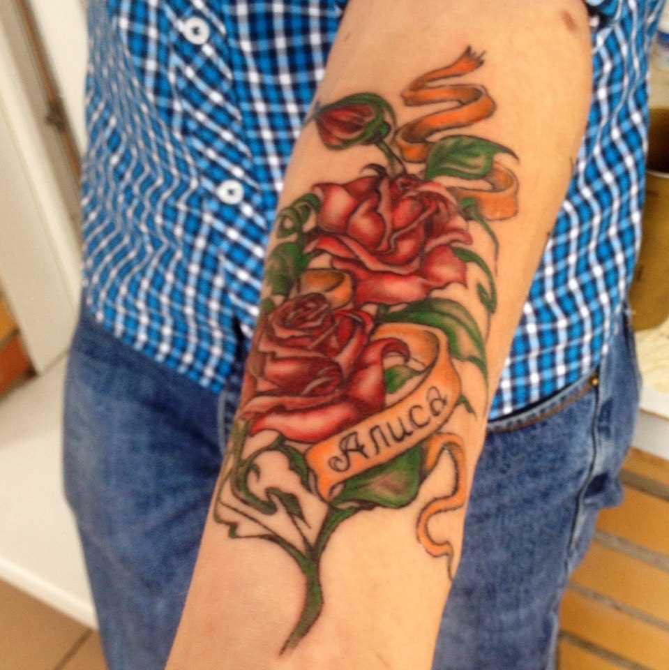 Tatuagem no antebraço do cara - de- rosa e um nome feminino