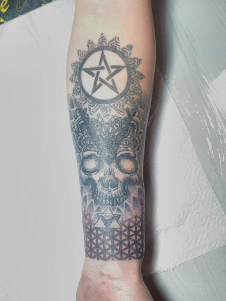 Tatuagem no antebraço do cara - o crânio e o pentagrama
