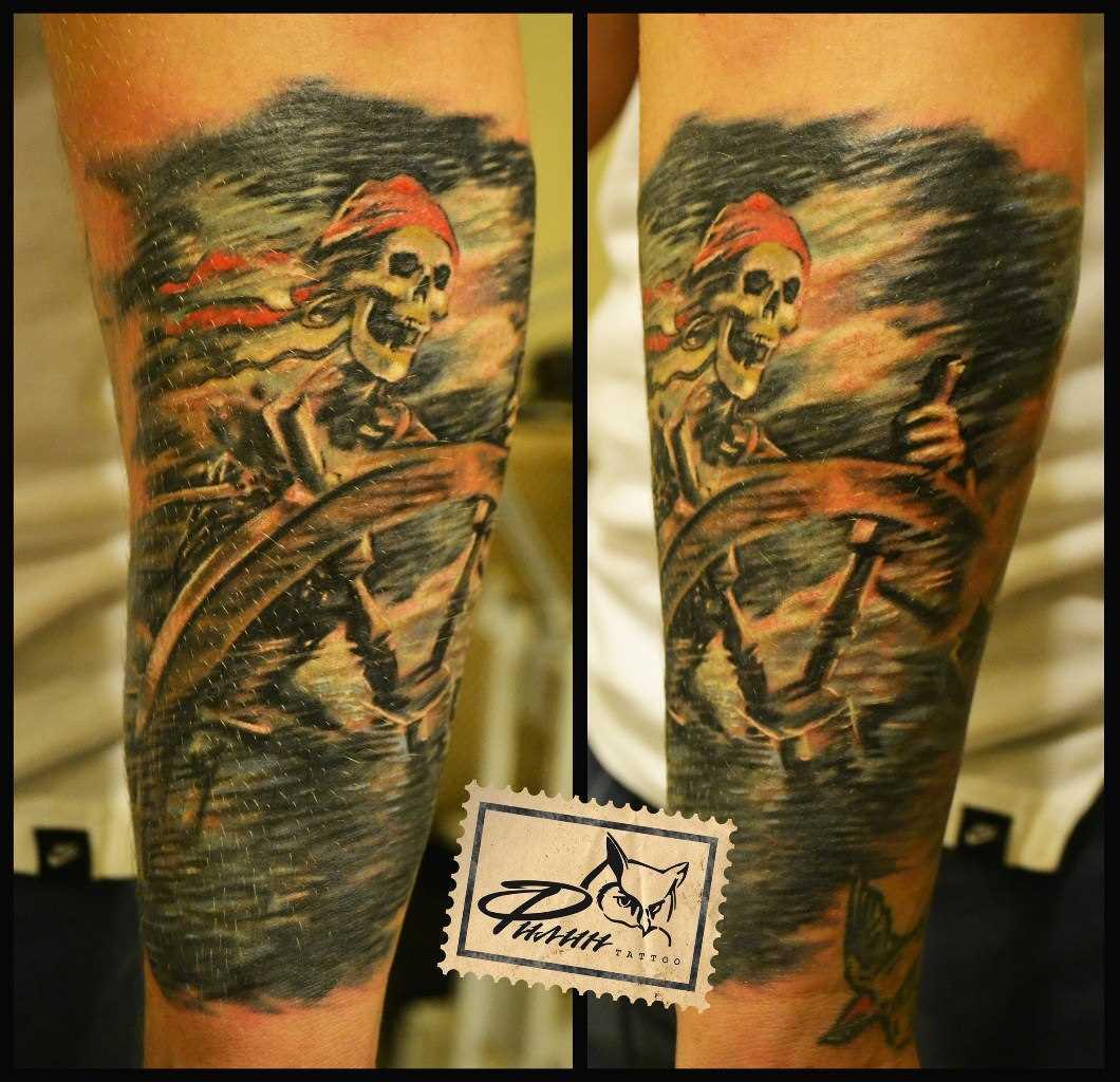 Tatuagem no antebraço do cara - o esqueleto e o leme