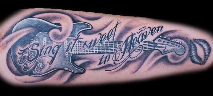 Tatuagem no antebraço tem um cara com uma guitarra e inscrição