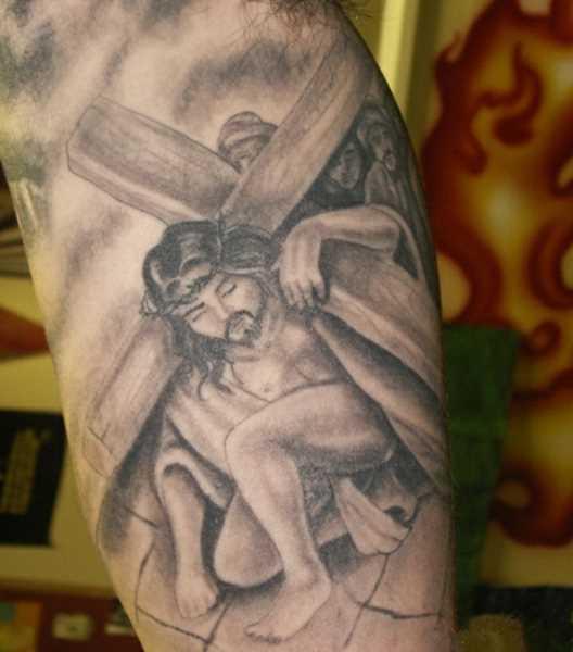 Tatuagem no braço de um cara - a cruz e Jesus, tendo-o