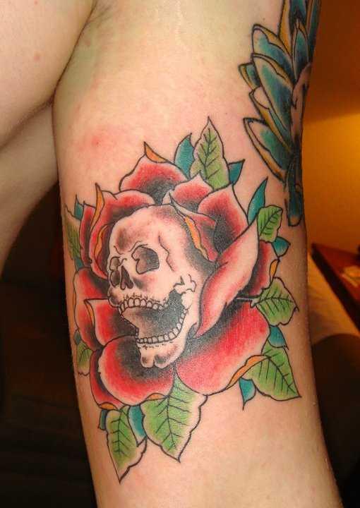 Tatuagem no braço de um cara - de- rosa e o crânio