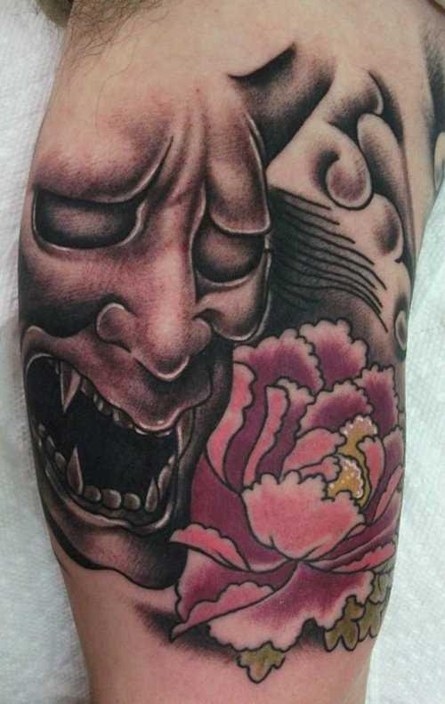Tatuagem no braço de um cara - ímpios máscara e peônia