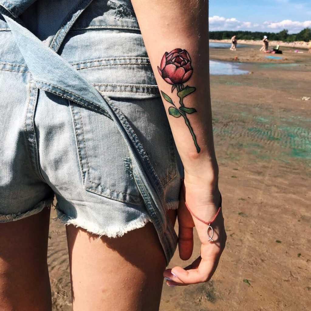 Tatuagem no braço de uma menina de rosa sobre a haste de