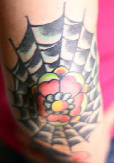 Tatuagem no cotovelo de meninas da web e florzinha