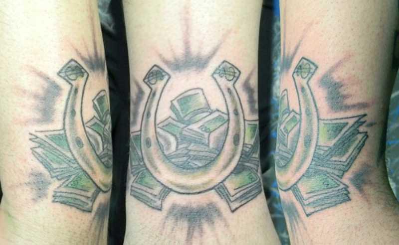 Tatuagem no cotovelo do cara - de- ferradura e o dinheiro