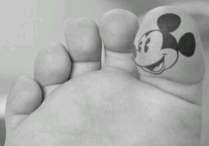 Tatuagem no dedo de uma menina - cabeça do rato Mickey Mouse