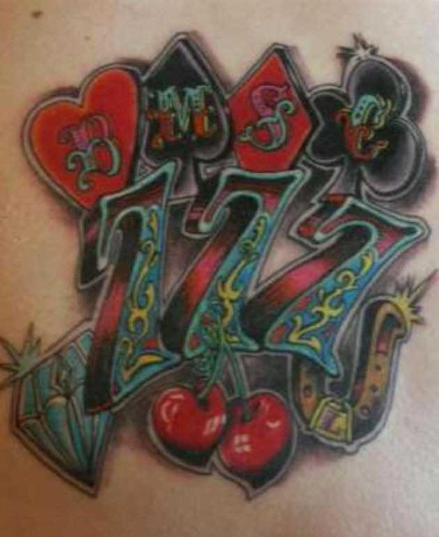Tatuagem no lado da menina - ferradura, o diamante, a cereja e o número 777