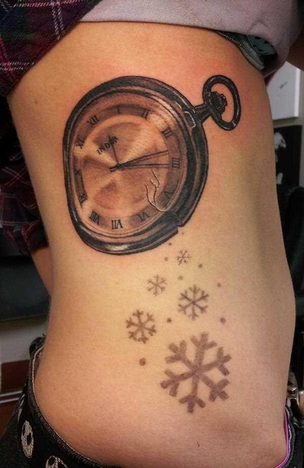 Tatuagem no lado da menina - relógio de bolso e flocos de neve
