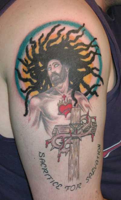Tatuagem no ombro da menina - a cruz e Jesus