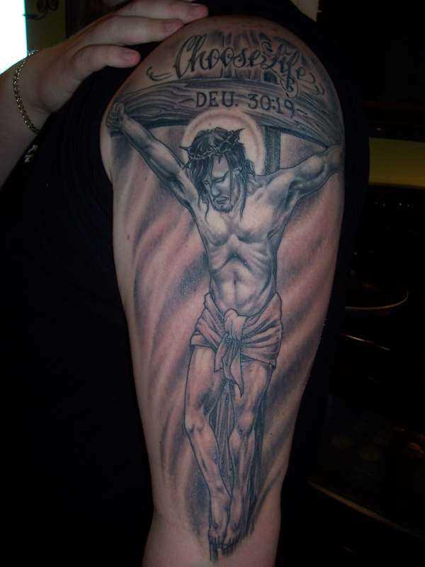 Tatuagem no ombro da menina - a cruz e o crucificado nela Jesus