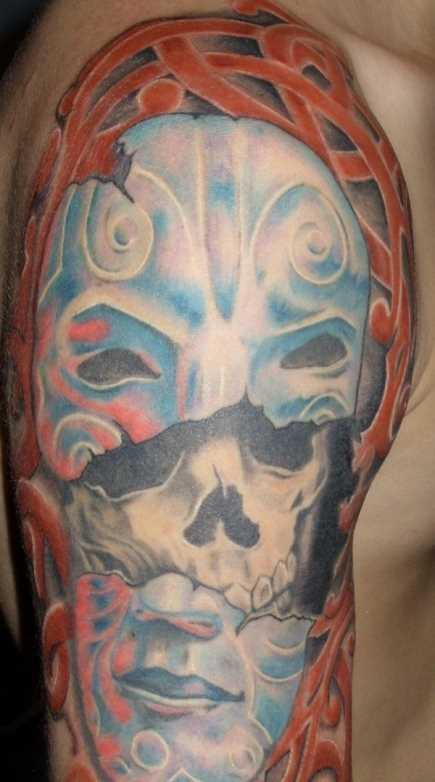 Tatuagem no ombro da menina - a máscara e o crânio