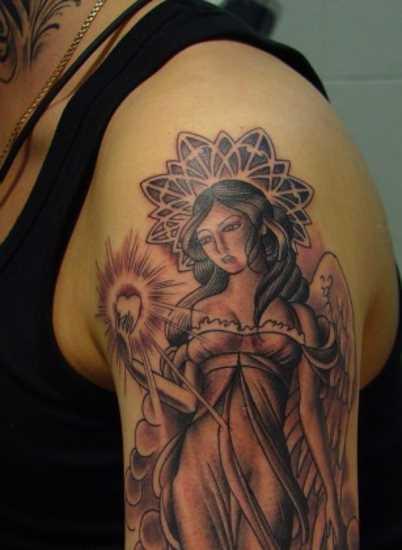 Tatuagem no ombro da menina - anjo com o coração