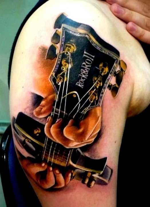 Tatuagem no ombro da menina com uma guitarra na mão