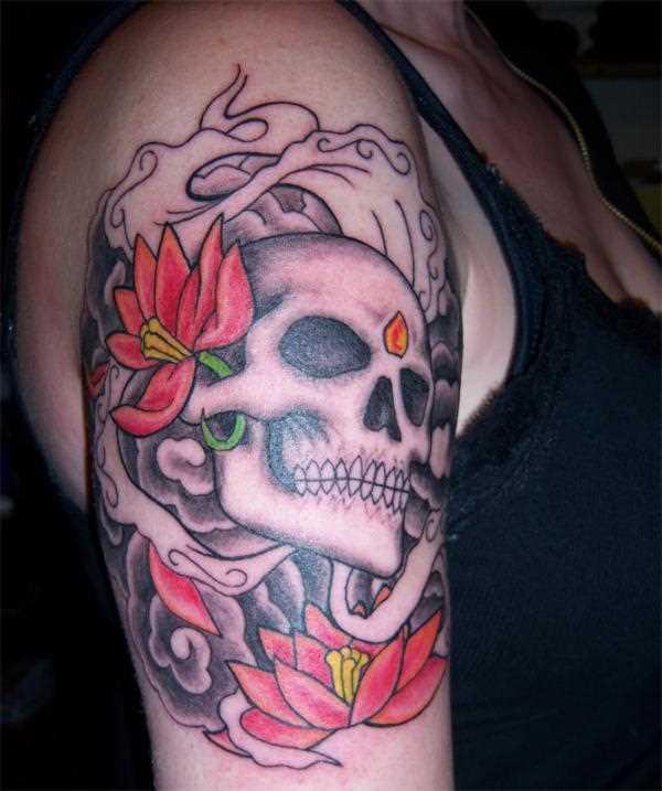Tatuagem no ombro da menina de crânio e de lótus
